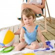 Stock Photo: Beach - Mother with child playing with toys in sand