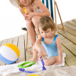 Beach - Mother with child playing with toys in sand — Stock Photo