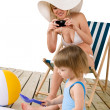 Stock Photo: Beach - Mother with child taking photo with camera