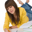 Foto de Stock  : Student - female teenager write homework with book