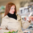 Shopping series - Red hair woman buying shampoo — Stock Photo