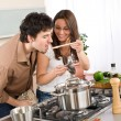 Couple cook in kitchen - man taste food — Stock Photo
