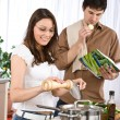 Happy couple cook together in modern kitchen — Stock Photo