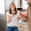 Young couple drink red wine in modern kitchen — Stock Photo