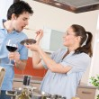Happy couple cook in kitchen tasting food — Stock Photo
