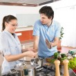 Stock Photo: Young happy couple cooking in kitchen