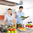 Young happy couple cook in kitchen with cookbook — Foto de Stock