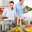 Young happy couple cook in kitchen with cookbook — Stock Photo