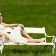 Spring - Young woman relaxing on bench in meadow — Stock Photo #4683567