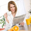 Breakfast - Smiling woman reading newspaper in kitchen — Stock Photo