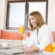 Breakfast - Smiling woman with orange juice in kitchen — Stock Photo
