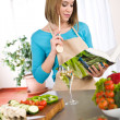 Cooking - Woman reading cookbook in kitchen — Stock Photo #4683718