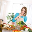 Cooking - Woman reading cookbook in kitchen - Stock Photo