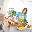 Cooking - Woman reading cookbook in kitchen — Stock Photo #4683723