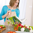 Cooking - Woman reading cookbook in kitchen — Stock Photo