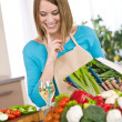 Cooking - Smiling woman holding cookbook, with vegetable and pas — Stock Photo #4683730