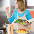 Stock Photo: Cooking - Young woman tasting tomato sauce in kitchen