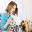 Cooking - Happy woman by stove in kitchen — Stock Photo