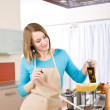 Cooking - Young woman with spaghetti on stove — Stock Photo