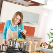 Cooking - Young woman with spaghetti on stove - Stock Photo
