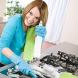 Young woman cleaning stove in kitchen — Stock Photo