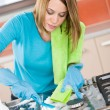 Stock Photo: Young womcleaning stove in kitchen