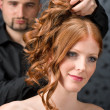 Professional hairdresser with fashion model at luxury salon - Photo