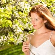 Young woman enjoying spring under blossom tree — Stock Photo