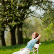 Young woman relaxing under blossom tree in spring - Stock Photo