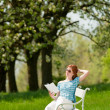 Young woman relaxing under blossom tree in spring — Стоковая фотография