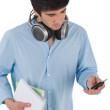 Stock Photo: Male student sending text message holding books