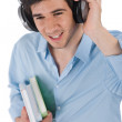 Male student with headphones holding books — Stok fotoğraf