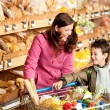 Stock Photo: Grocery store shopping - Woman with child in winter outfit