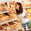 Grocery store: Young woman holding shopping basket — Foto de Stock