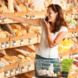Grocery store: Young woman holding mobile phone — Stock Photo