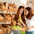 Stock Photo: Grocery store: Two women choosing bread