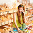 Grocery store: Red hair woman with mobile phone — Stock Photo