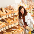 Stock Photo: Grocery store: Young woman buying bread