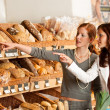 Grocery store: Two young women choosing bread — Stock Photo
