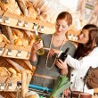 Grocery store: Two young women choosing wine — Stok fotoğraf