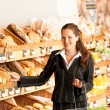 Stock Photo: Grocery store: Business woman choosing bread