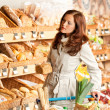 Grocery store: Young woman choosing bread — Stock Photo