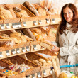 Grocery store: Young woman choosing bread — Stock Photo #4684236