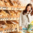 Grocery store: Young brown hair woman with mobile phone — Stock Photo #4684238