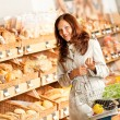 Grocery store: Young woman in bakery department - Foto de Stock