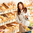 Grocery store: Young woman with shopping basket — Stok fotoğraf