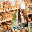 Grocery store shopping - Happy woman with child — Stock Photo #4684249