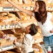 Grocery store shopping - Young woman with child — Stock Photo