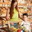 Royalty-Free Stock Photo: Grocery store shopping - Red hair woman with little boy