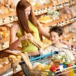 Grocery store shopping - Woman and child buying bread — Stock Photo